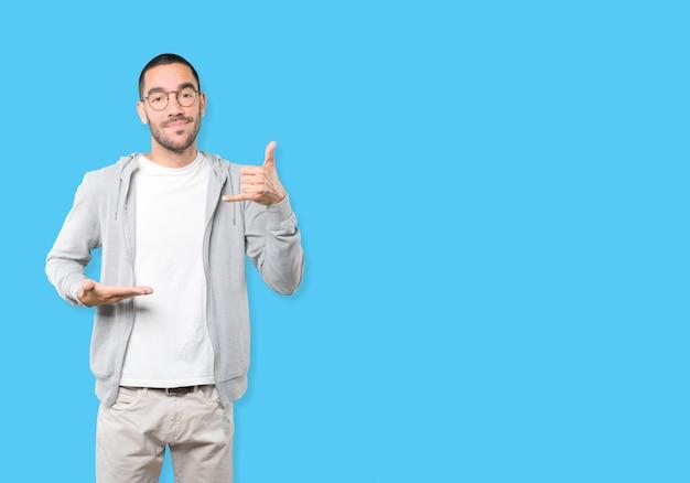 Сомневающийся молодой человек делает жест вызова с рукой