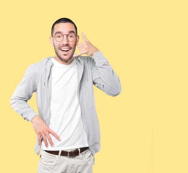 手で呼び出すのジェスチャーを作る驚いた若い男