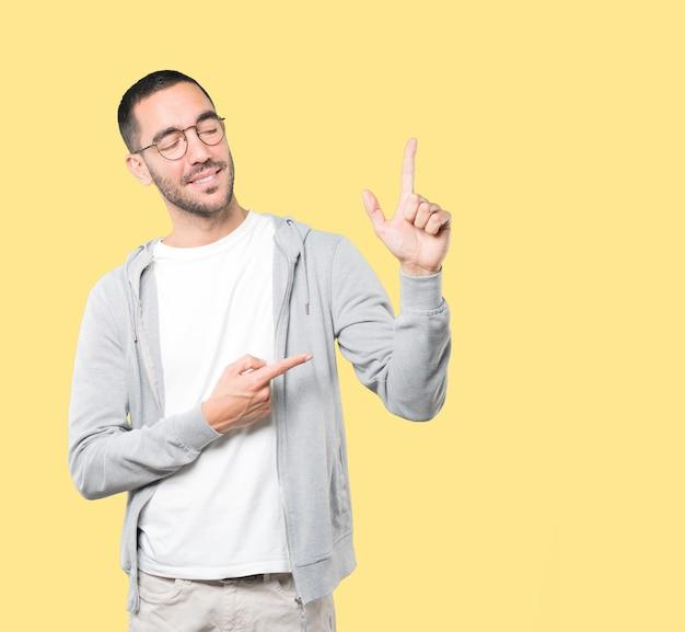 Молодой человек делает жест номер два