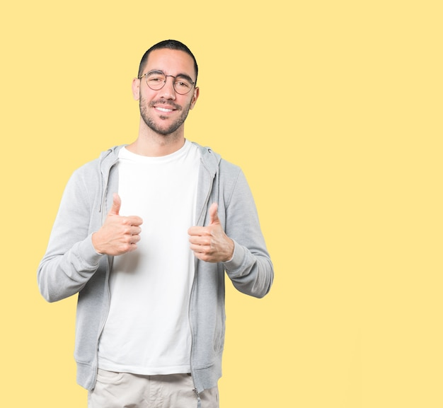 すべてがうまくいっていることを身振りで示す幸せな若い男