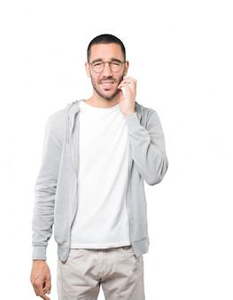 Обеспокоенный молодой человек делает царапающий жест