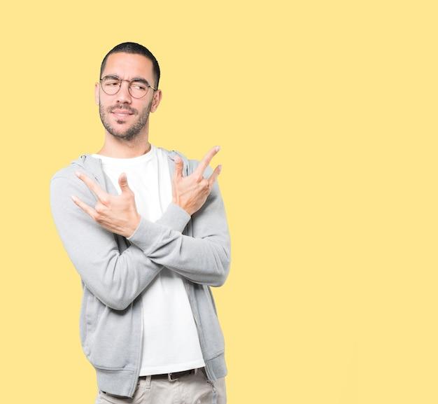 Непослушный молодой человек делает жест рок