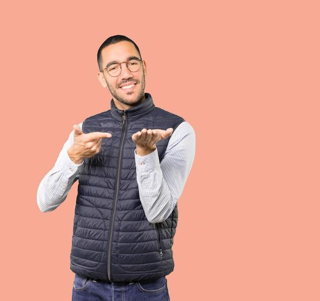 Счастливый молодой человек держит что-то с его рукой