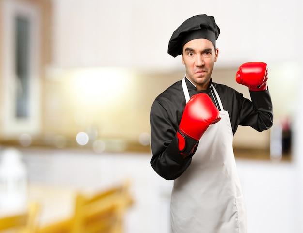 Сердитый шеф-повар, используя боксерские перчатки