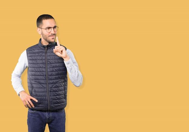 Серьезный молодой человек просит молчания, указывая пальцем