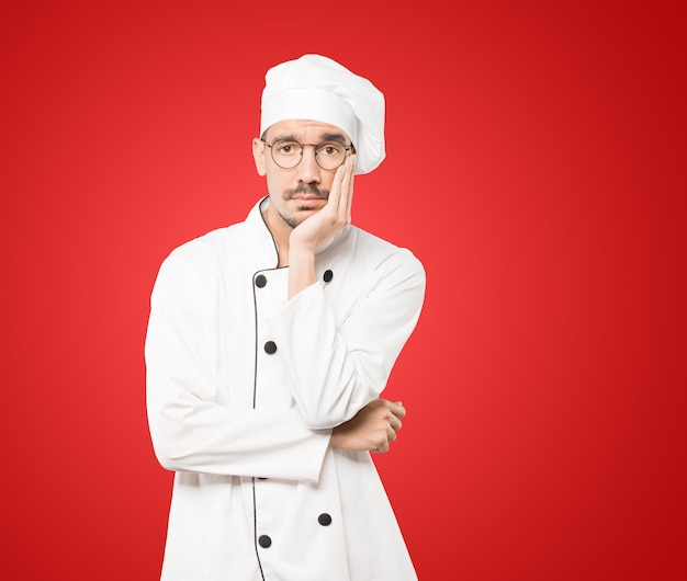 Усталый молодой шеф-повар делает жест скуки