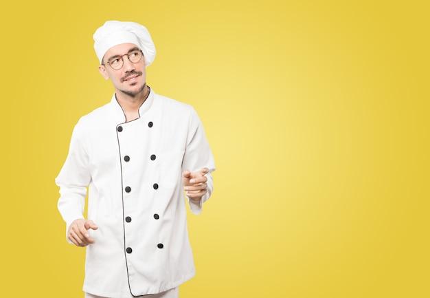 Дружелюбный молодой повар делает жест восхищения