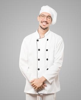 Счастливый молодой шеф-повар позирует