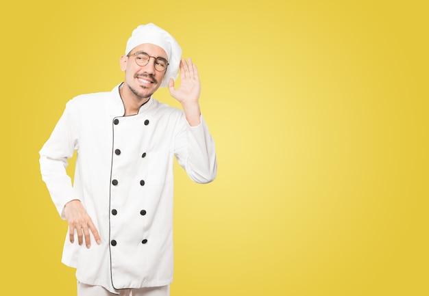 Счастливый молодой шеф-повар улыбается и делает жест, пытаясь услышать что-то