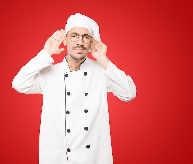 Сконцентрированный молодой повар делает жест, пытаясь что-то услышать