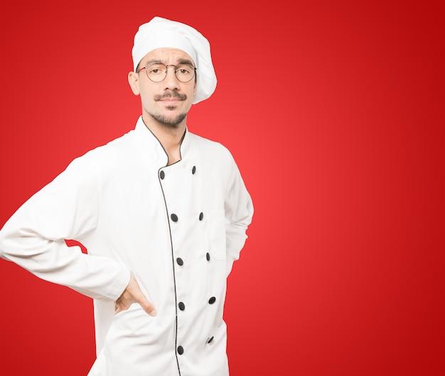 Сомневающийся молодой шеф-повар, глядя вверх жест