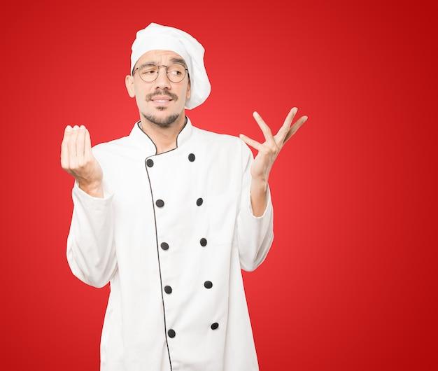 Смущенный молодой шеф-повар делает итальянский жест не понимаю