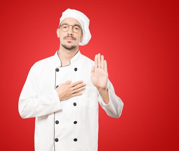 Серьезный молодой повар с жестом клятвы