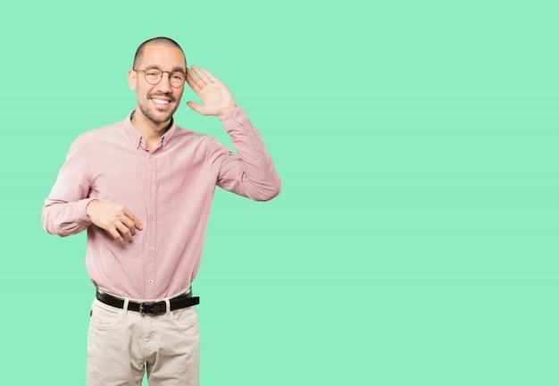 Счастливый молодой человек улыбается и делает жест пытается что-то услышать