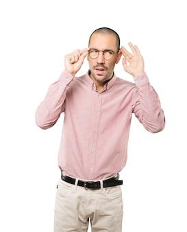 Сконцентрированный молодой человек делает жест, пытаясь что-то услышать
