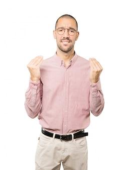 Смущенный молодой человек делает итальянский жест не понимаю