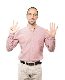 Счастливый молодой человек делает жест номер восемь своими руками