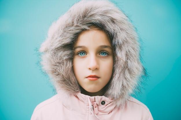 Красивый голубоглазый ребенок смотрит в розовое пальто