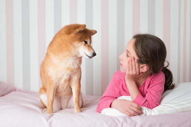 彼女のピンクのベッドに座っているパジャマで小さな女の子を探している柴犬の品種犬