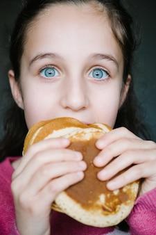 いくつかの自家製パンケーキを楽しみにして、青い目の白人の女の子のクローズアップの肖像画。ライフスタイルのコンセプト