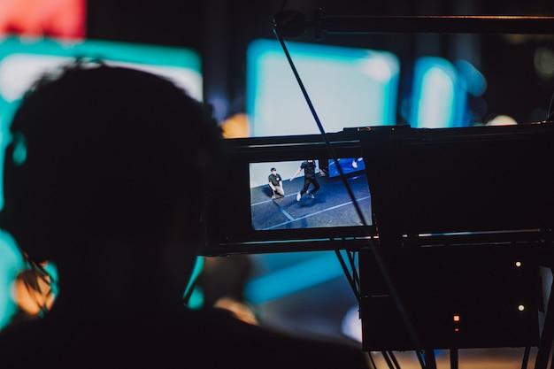 Профессиональный видео оператор, снимающий развлечения на сцене