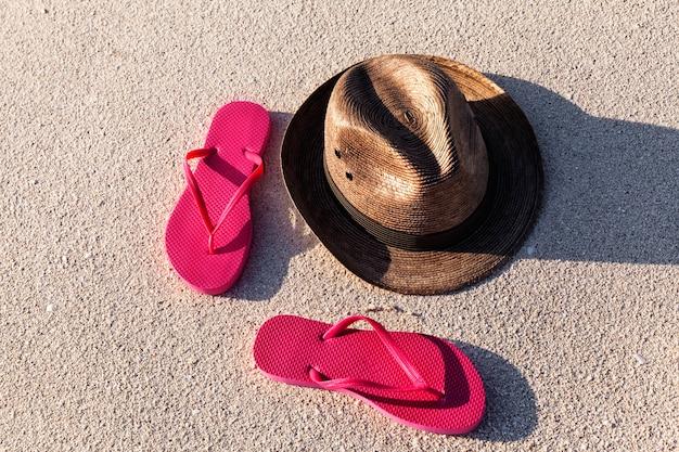 Летние розовые шлепанцы и соломенная шляпа на песчаном пляже в солнечный день