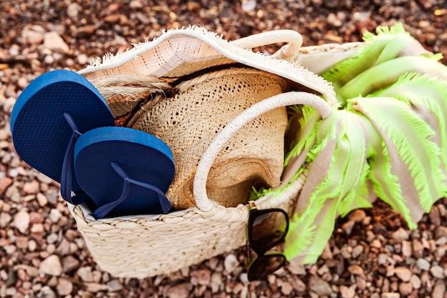 ストローバッグ、帽子、サングラス、海岸のフリップフロップのクローズアップ