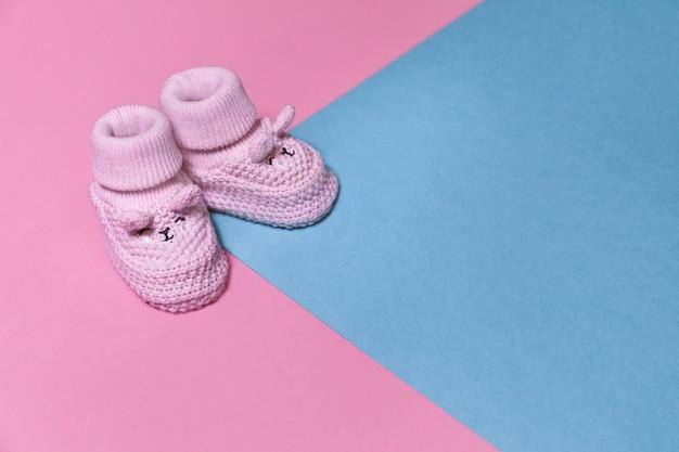 コピースペースでパステル紙の背景にピンクの新生児ニットシューズ