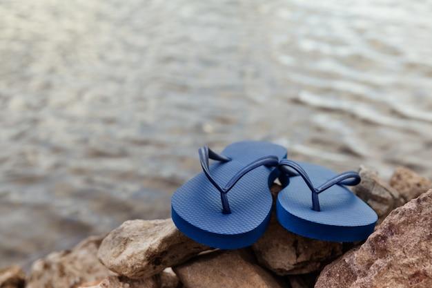 夏の時間で岩のビーチで青いフリップフロップのクローズアップ