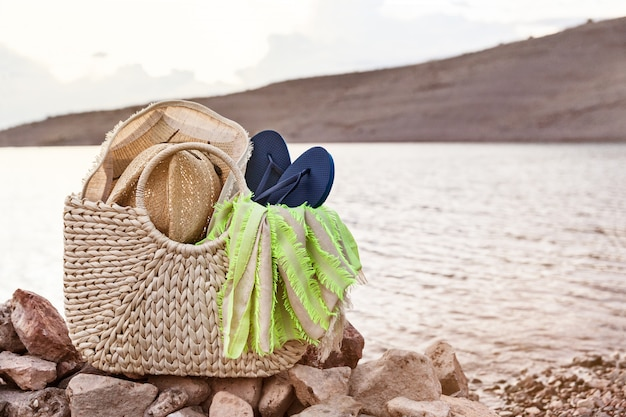 Летние аксессуары в соломенной сумке на берегу, концепция отдыха