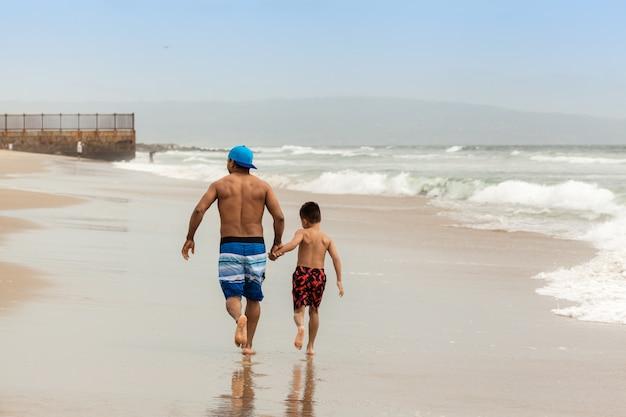 夏のビーチで一緒に歩いて手を繋いでいる父と息子