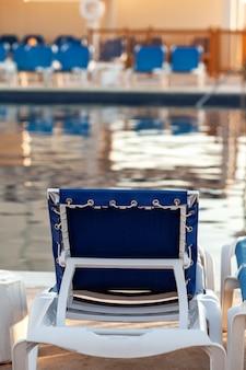 朝、休暇、旅行のスイミングプールで空の椅子