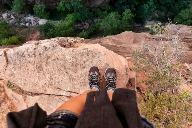 峡谷を見下ろす岩の端に立っている若い女性
