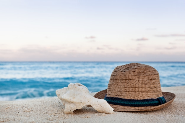 日の出の砂浜で夏の麦わら帽子と海のシェル