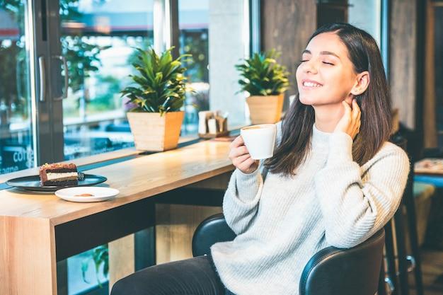 Счастливая молодая женщина с чашкой кофе, сидя у окна в кафе с закрытыми глазами