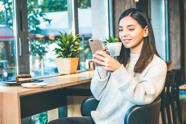 Счастливая молодая женщина с чашкой кофе, сидя у окна в кафе, в чате на телефоне