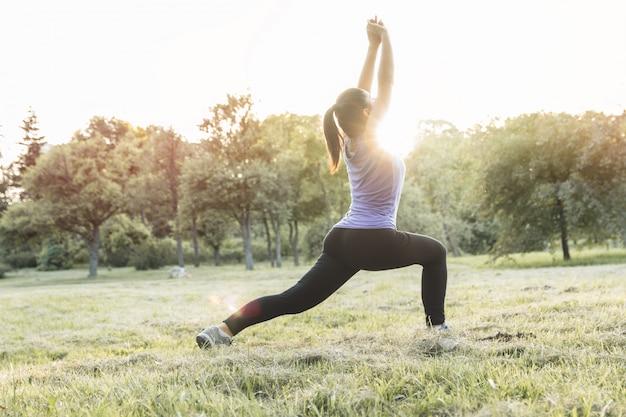 日の出や日没の屋外トレーニング、ヨガ、フィットネスの前にウォーミングアップスポーティな女性。