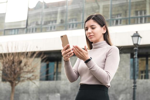 Молодая деловая женщина смотрит на свой телефон