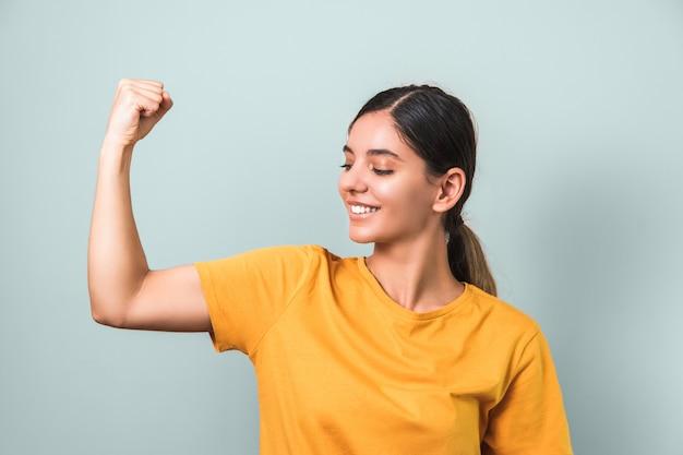 Женщины сильны. молодая привлекательная брюнетка в желтой футболке показывает бицепс на светло-зеленом фоне