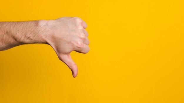 良くない、承認されていない。黄色の背景に嫌いなサインを親指を示す男の手を閉じる