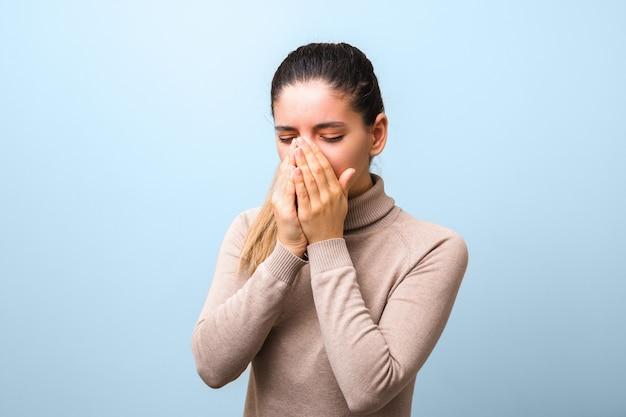 発熱と頭痛のくしゃみと咳と絶望的な女性。