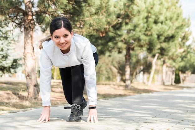 健康的な生活様式。陽気な魅力的な女性は朝の松の木が公園で走り始める準備ができて