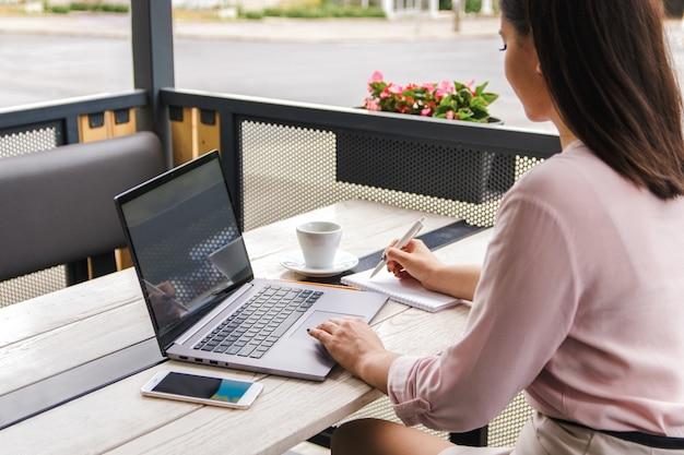 Ориентирован на работу. привлекательный молодой предприниматель, фрилансер или студент работает на ноутбуке и делать заметки в своем блокноте на террасе в кафе