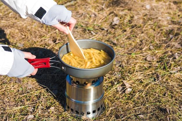 野生のキャンプでウッドバーナーでパスタを調理する女性ハイカーの手を閉じる