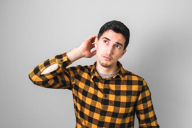 愚かな灰色の背景に対して黄色の背景で思慮深いハンサムな男