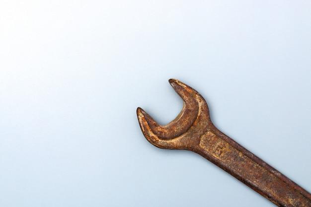 Старый ржавый гаечный ключ на чистом сером фоне с копией пространства