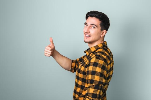 いいね。大きな親指を現してハンサムなブルネット若い男