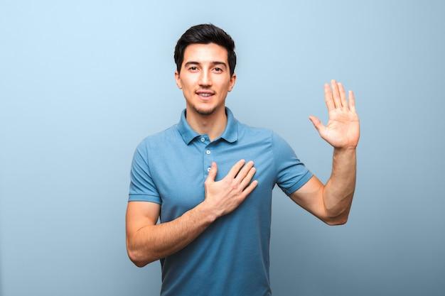 Красивый молодой человек с нейтральной улыбкой в синей рубашке поло с рукой на груди дает клятву