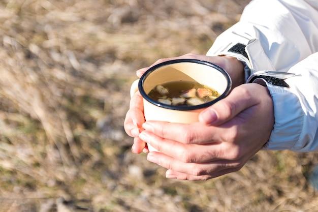 野の花からお茶と金属マグを保持している女性ハイカーの手を閉じる