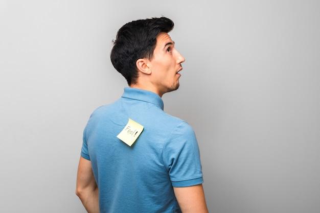 Глупый мужчина в синей рубашке с желтой запиской со словом дурак на спине тупо смотрит вверх